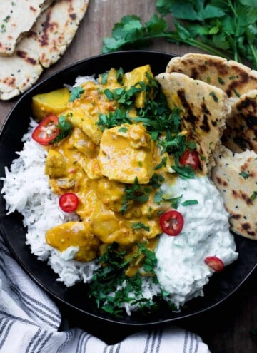 A bowl of The Best Totally Creamy Leftover Turkey Curry with naan bread, raita and rice