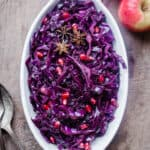 Braised Red Cabbage sprinkled with pomegranate seeds and star anise in a white dish on a wooden board