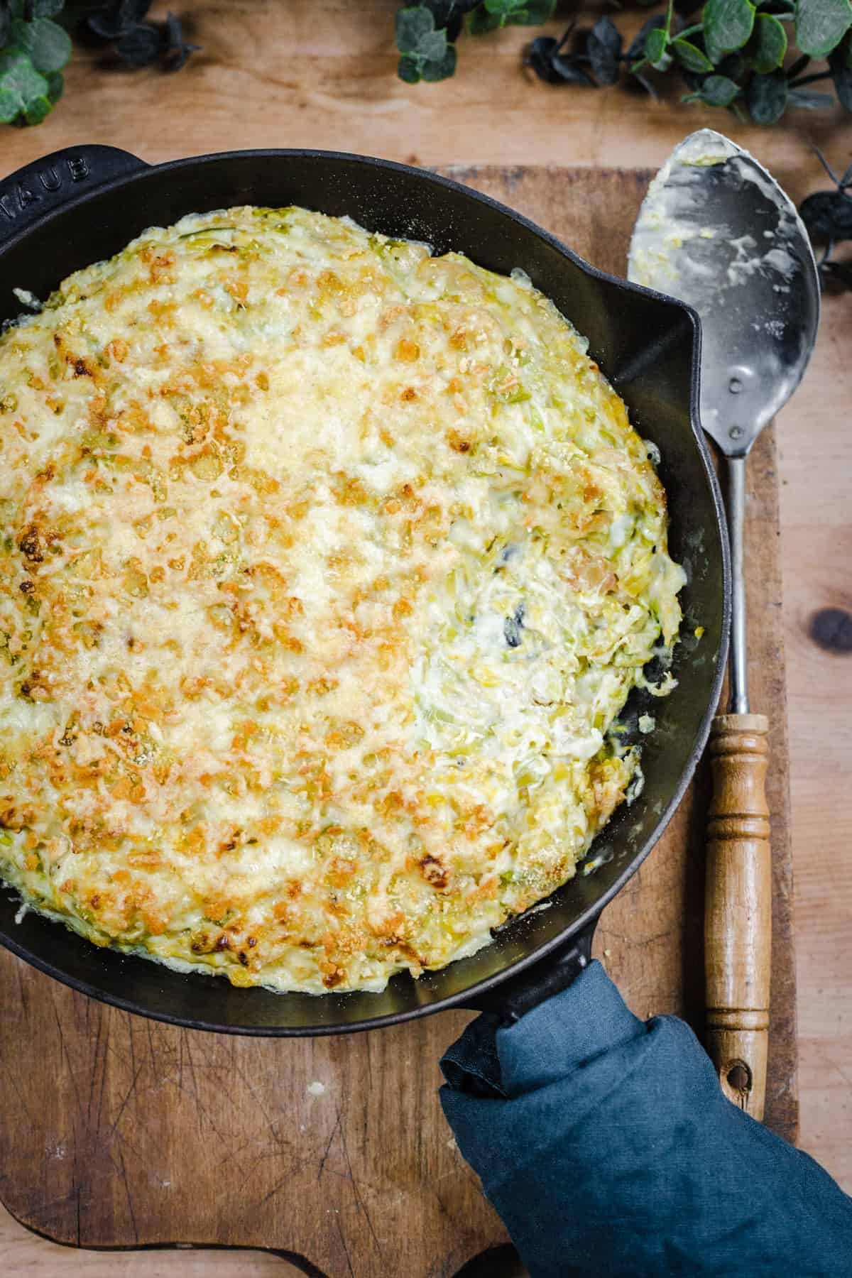Cheesy & Creamy Brussels Sprouts Gratin in a cast iron pan on wooden board