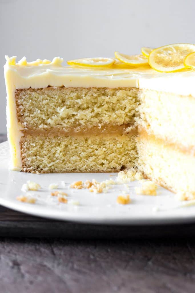 lemon curd cake cut into on a white plate