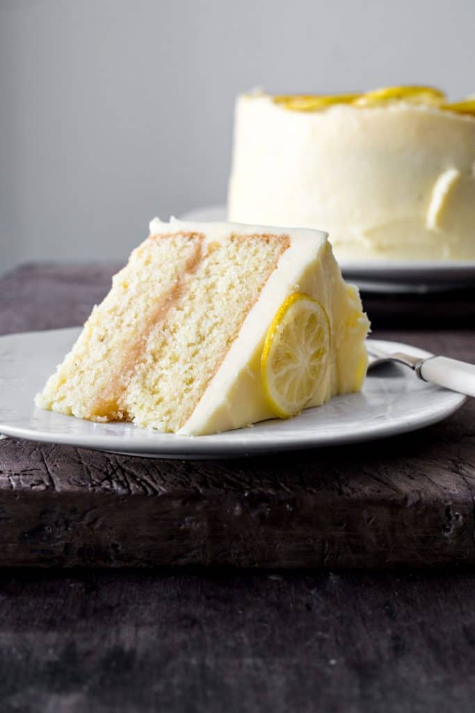 A slice of lemon curd cake on a plate on a wooden table