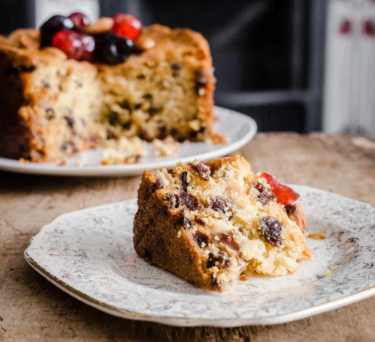 A slice of Gluten-Free Fruit Cake on a plate in front of the rest of the cake