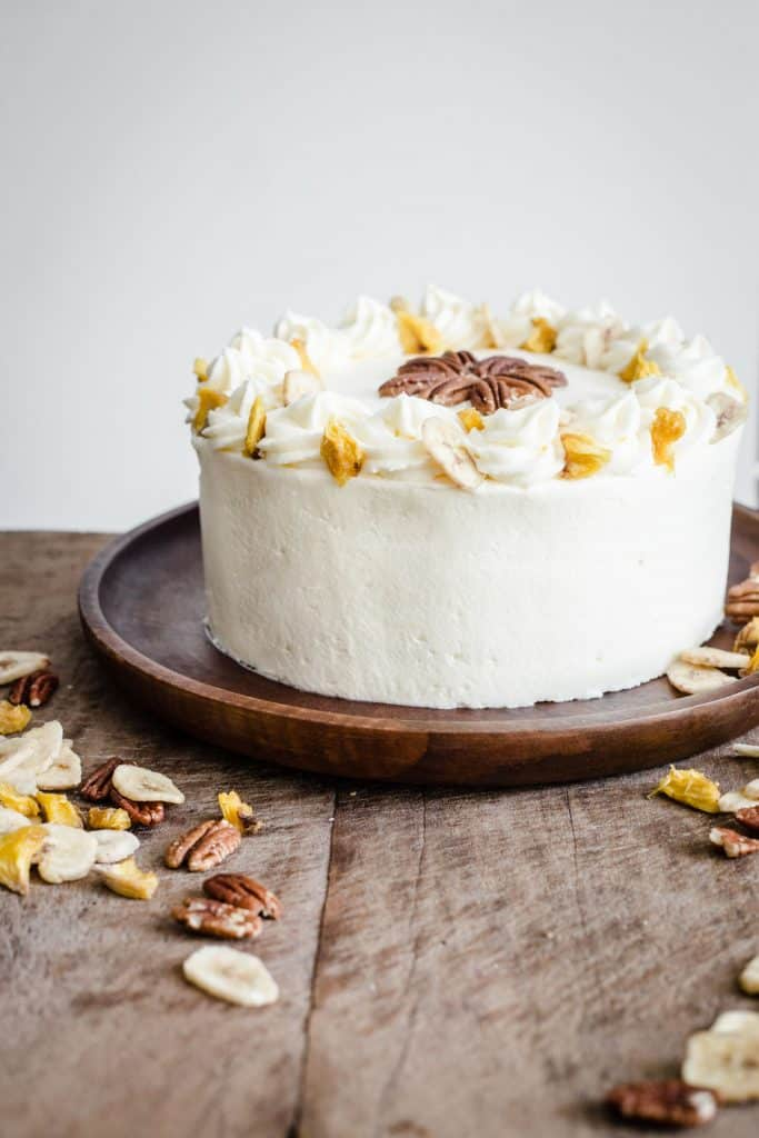 Gluten-Free Hummingbird Cake on a wooden place surrounded by dried fruit and nuts