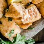Close up of salmon nugget broken apart on a plate