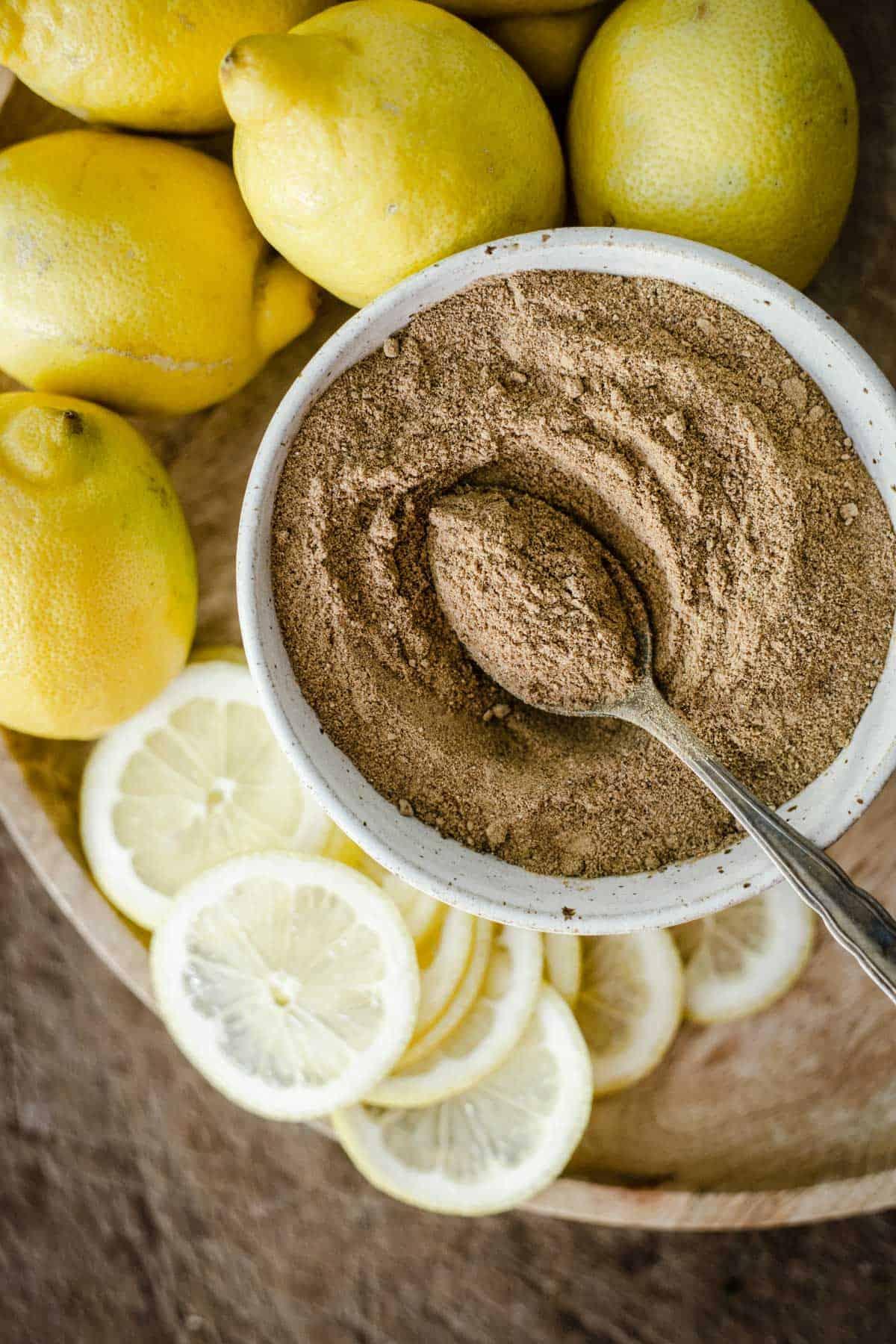 homemade lemon powder in a bowl surrounded by lemons