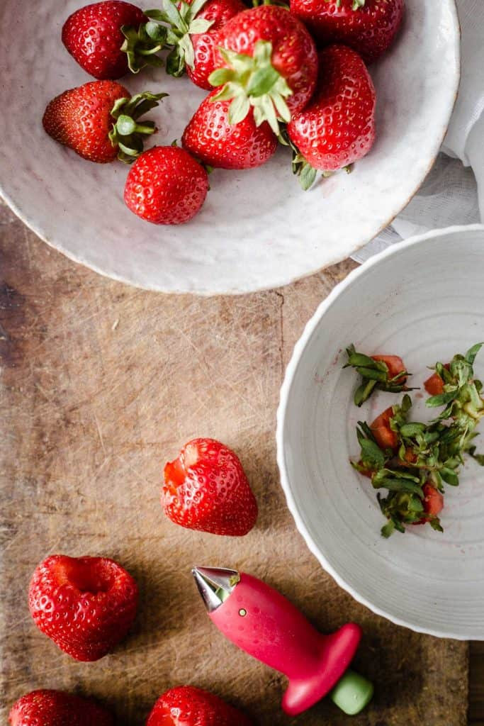 hulled strawberries on a board with strawberry stalks and whole strawberries in separate bowls