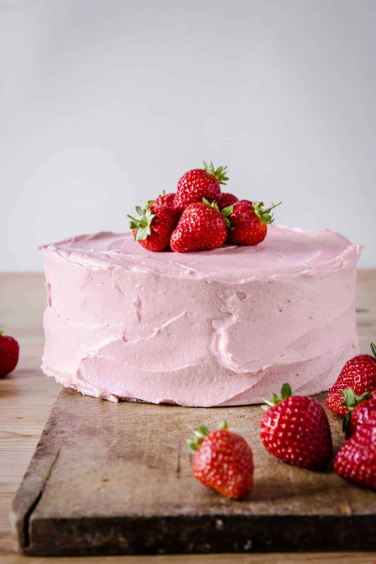 strawberry cake on wooden board surrounded by strawberries