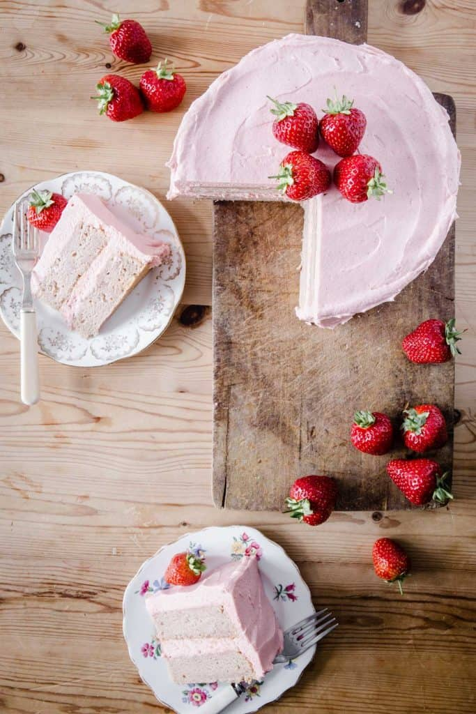 overhead view of strawberry cake on wooden board surrounded by strawberries and slices of cake