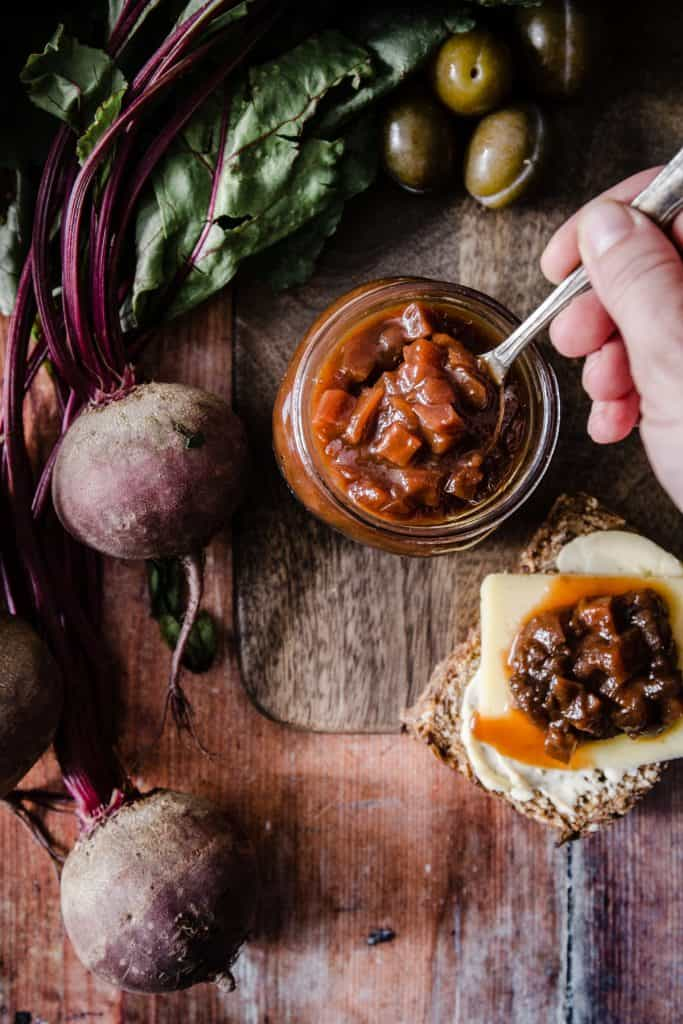 spoon digging into a pot of chutney surrounded by the raw ingredients and chutney on bread