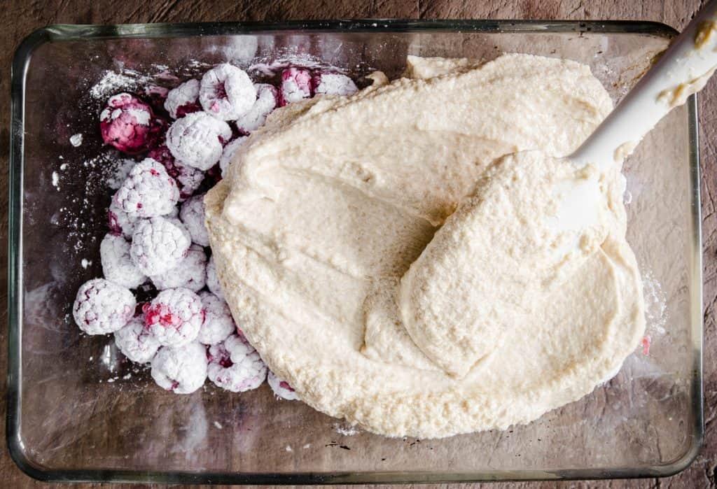 sponge batter covering raspberries in baking dish