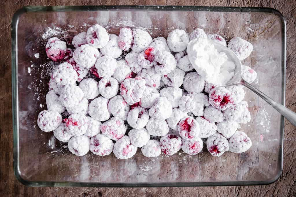 Raspberries tossed in tapioca flour at the bottom of a glass baking dish