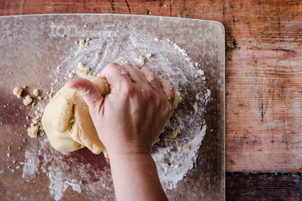 hand kneading gluten free pastry on wooden board
