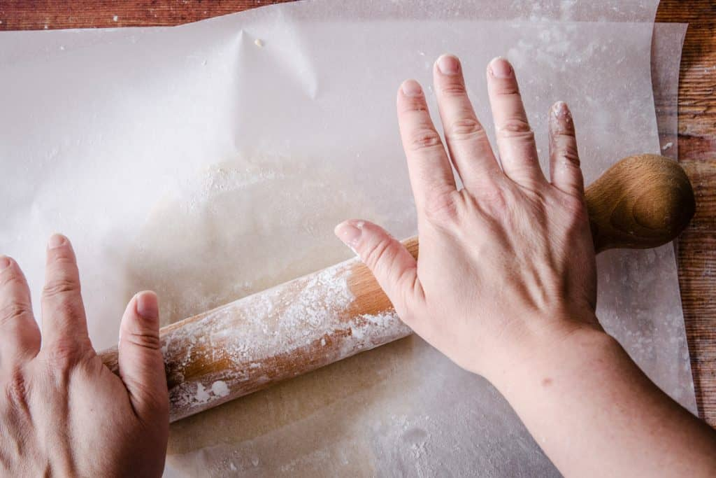 hands rolling out gluten free pastry between parchment paper