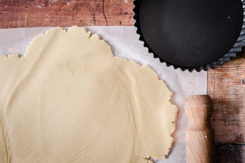 rolled out gluten-free pastry next to tart tin