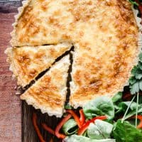 gluten-free quiche on a wooden board surrounded by salad