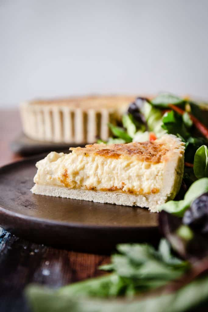 A slice of gluten-free quiche on a wooden plate surrounded by salad