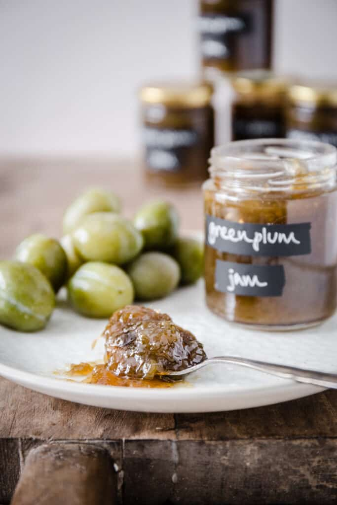 Green plum jam on a spoon on a plate with a jar of jam and green plums