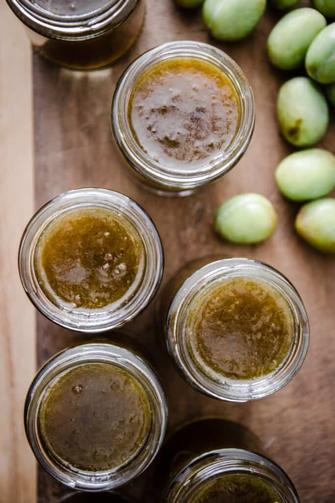 overhead shot of jars of green plum jam on a wooden board