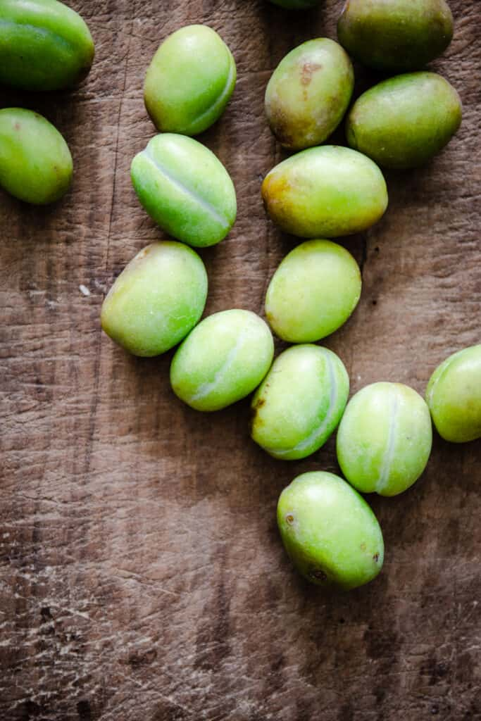 Green plums on a wooden board