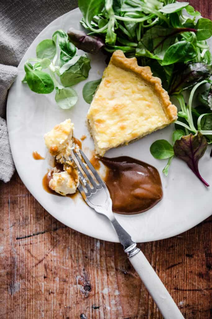 plate of brown sauce with quiche and a fork taking a bite.