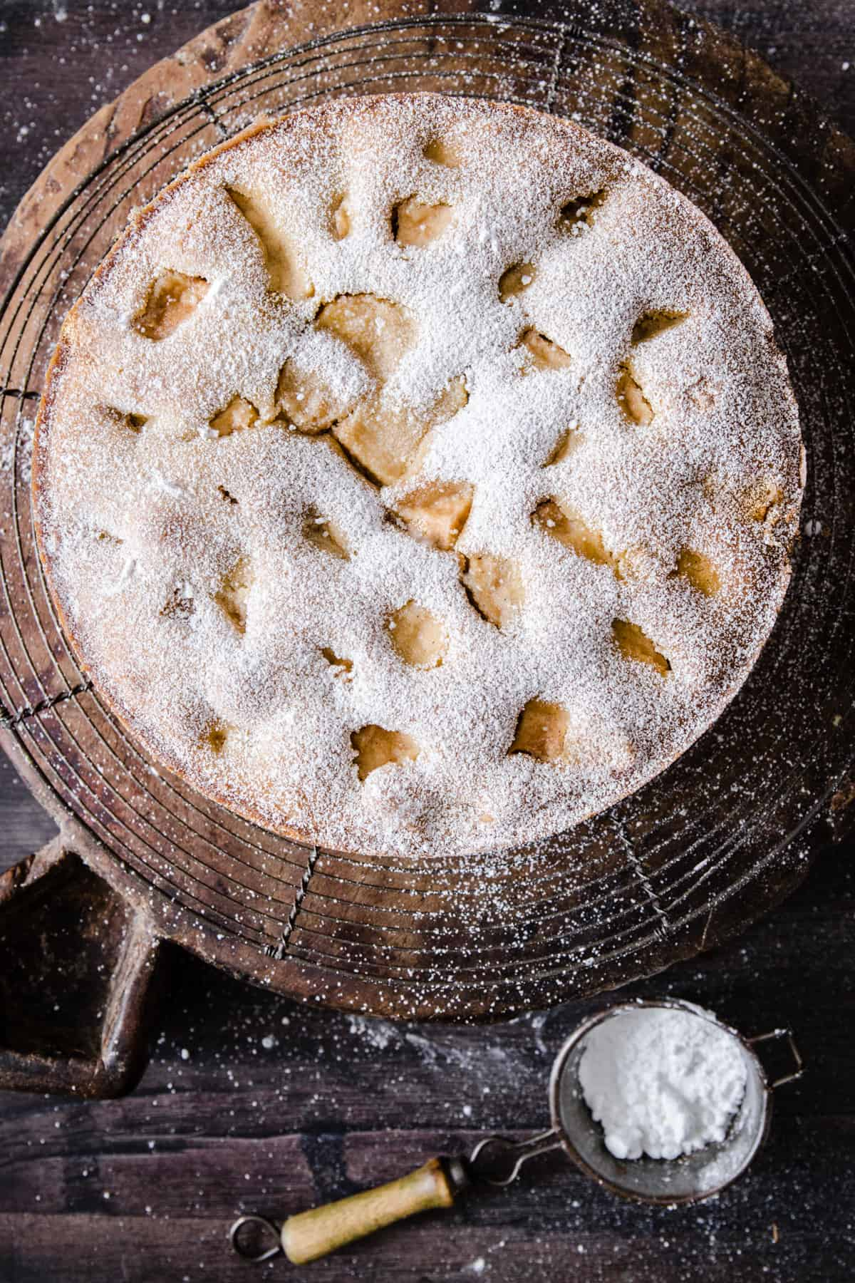 Apple cake on a cooling rack next to a knife and a sifter of icing sugar