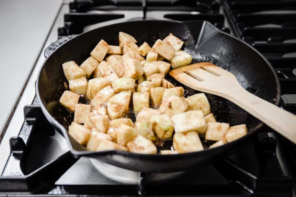 Cubes of apple caramelising in a pan