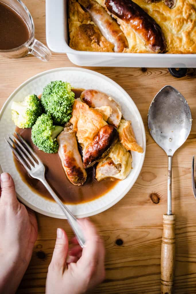 a portion of Toad in the Hole on a plate with broccoli and gravy and a hand going into pick up the fork