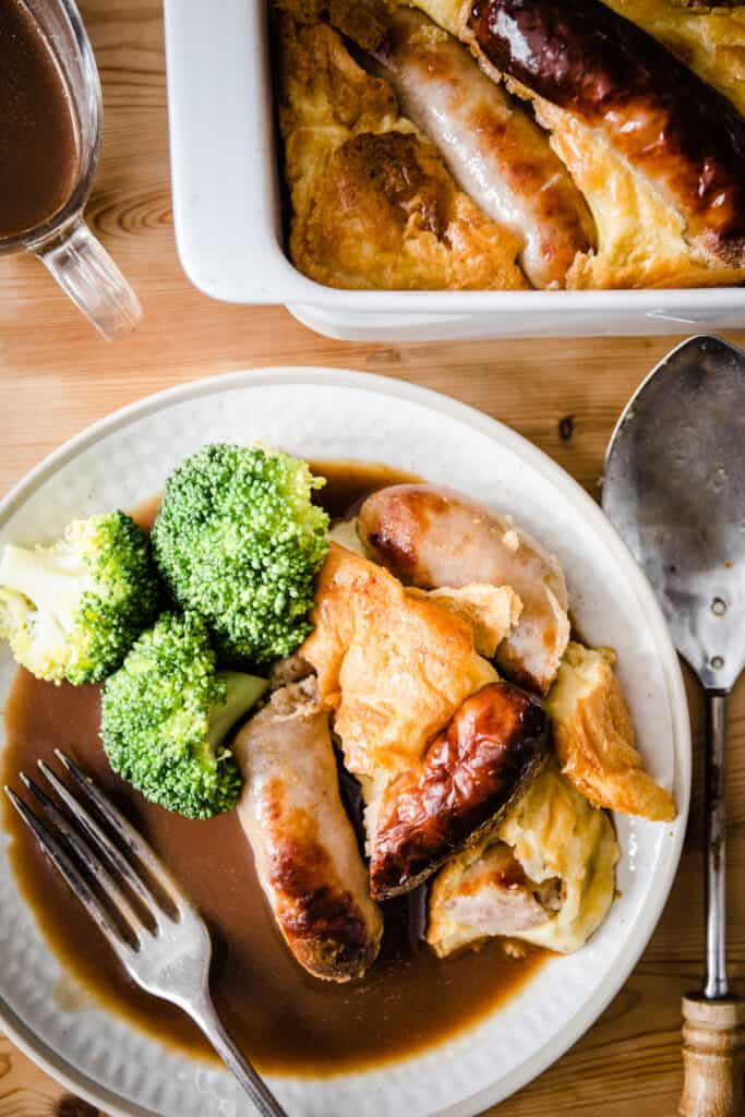 a portion of Toad in the Hole on a plate with broccoli and gravy