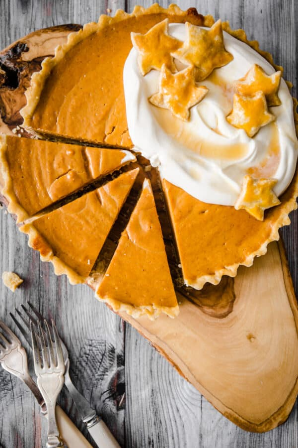 overhead image of pumpkin pie with slices cut out