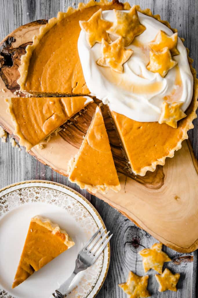 overhead image of pumpkin pie with slices cut out and a slice of pumpkin pie on a plate
