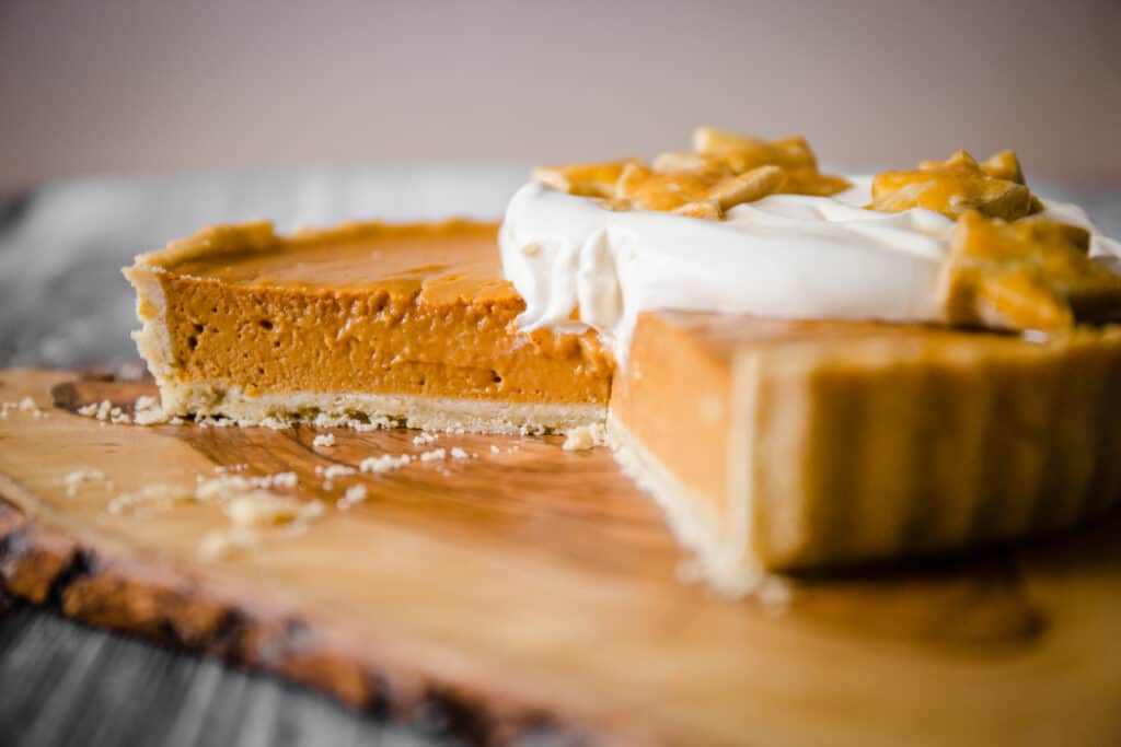 Pumpkin pie on a wooden board with a slice taken out