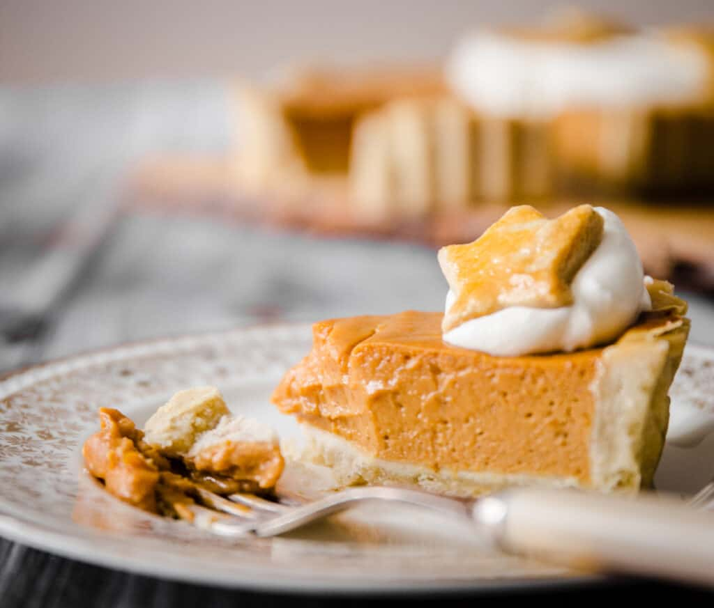 A slice of pumpkin pie with a forkful taken out
