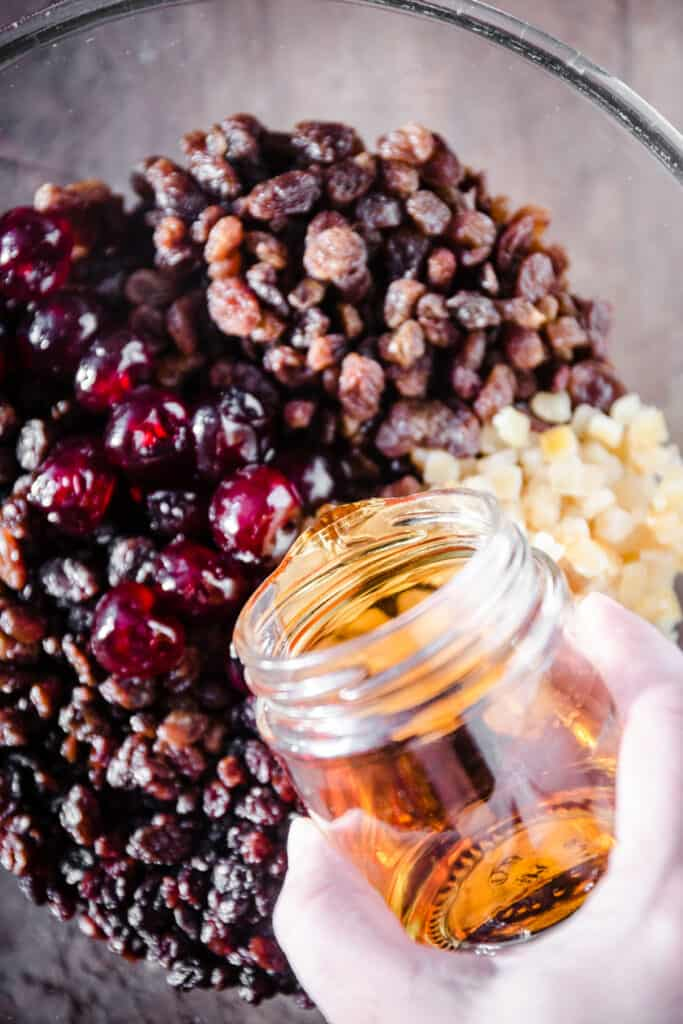 brandy being poured into dried fruits in glass bowl