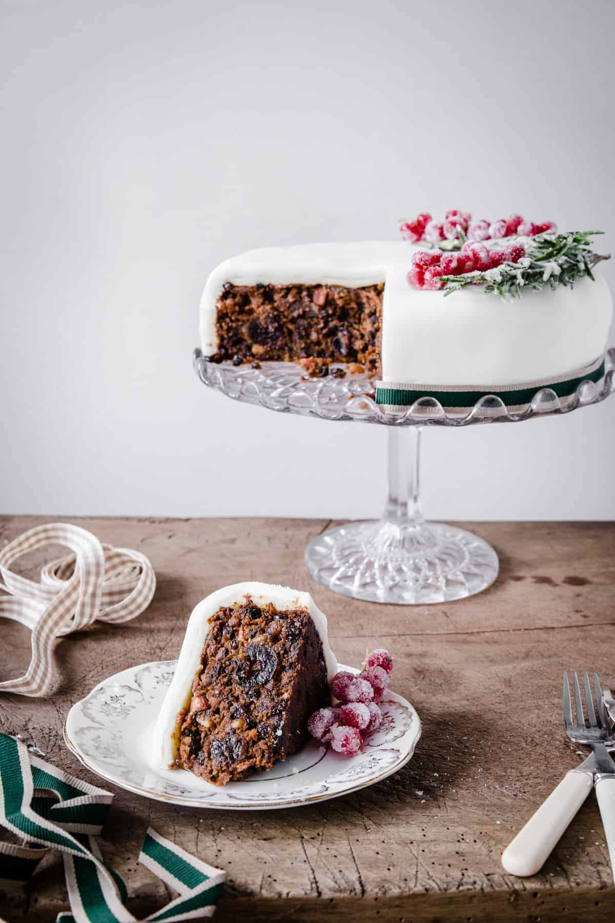 Slice of Christmas Cake on a plate in front of whole cake on a stand