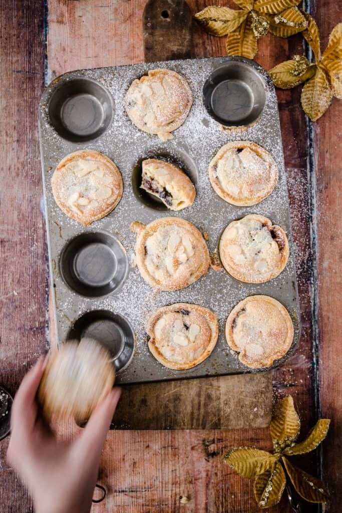 Hand grabbing a Frangipane Mince Pie from the baking tin filled with mince pies