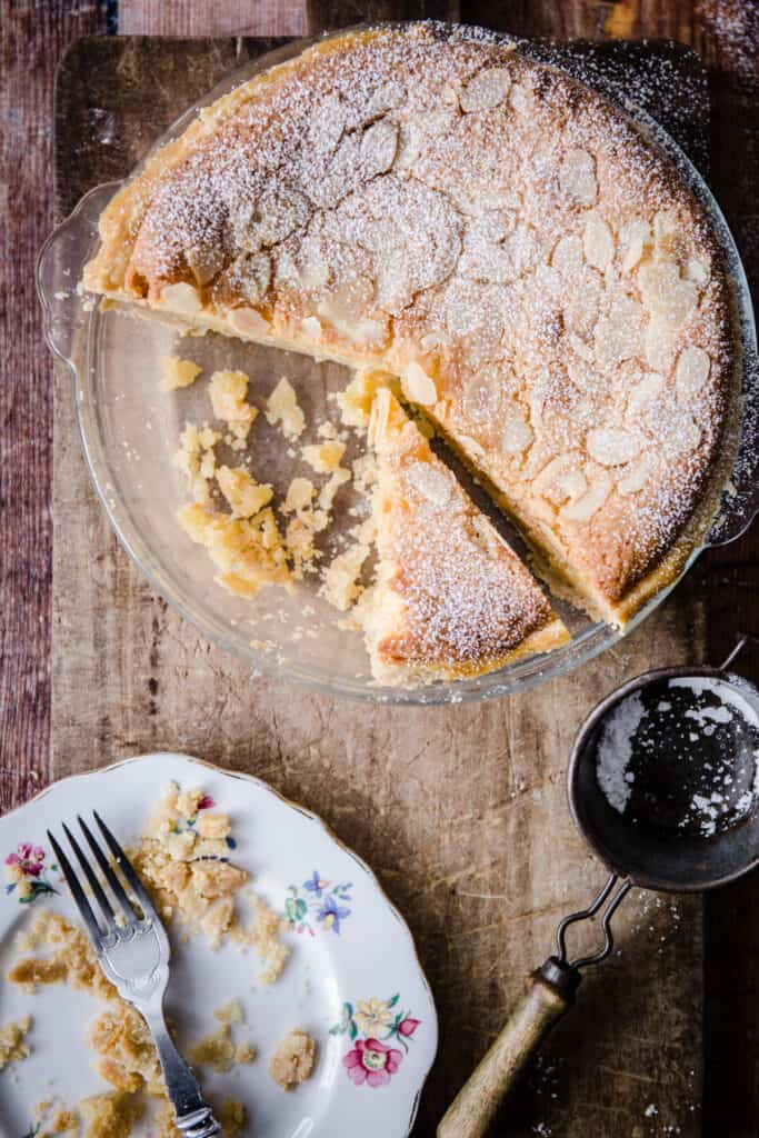 Gluten-Free Frangipane Tart sliced and sitting on wooden board next to plate with a fork and crumbs