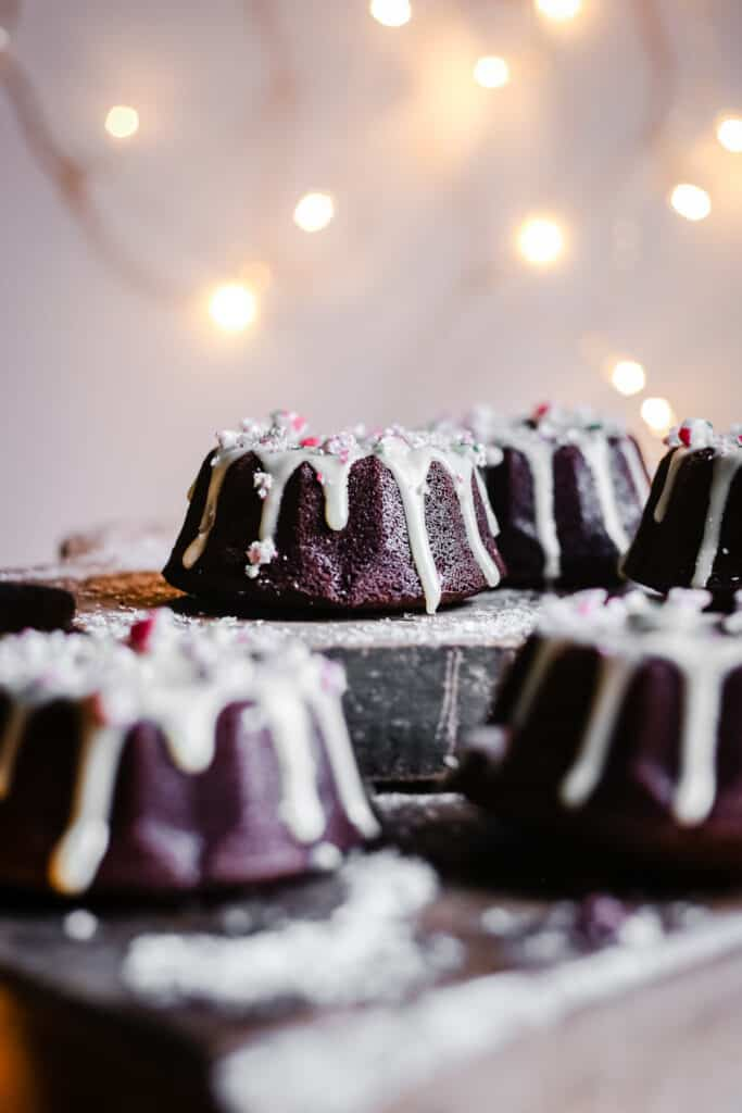 Mini Chocolate Bundt Cakes on wooden boards surrounded by fairy lights
