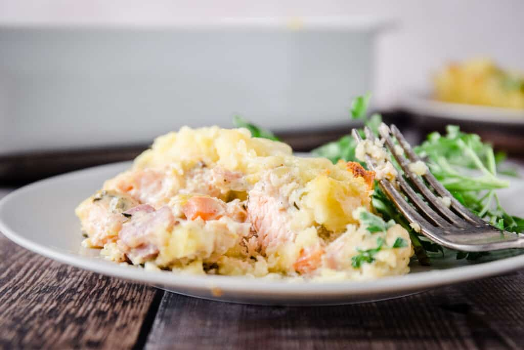 Salmon fish pie on a plate with a fork