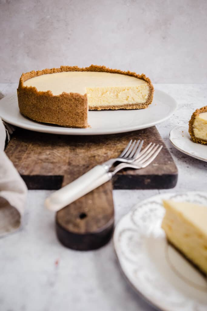 whole cheesecake on wooden board with slice taken out. Forks next to it.