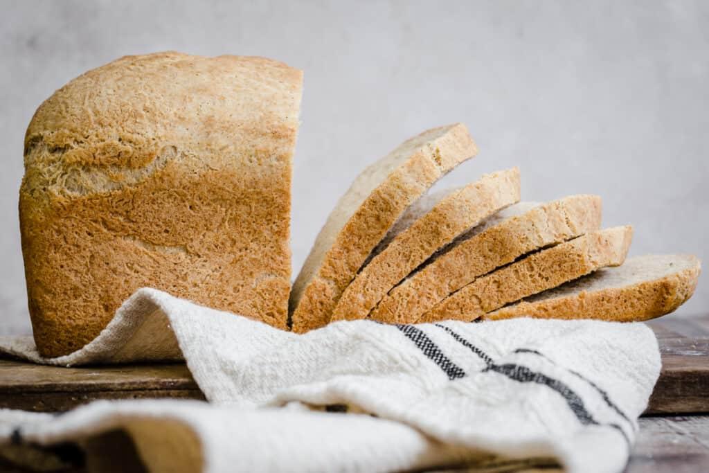 sliced gluten free bread on a cloth on a wooden board