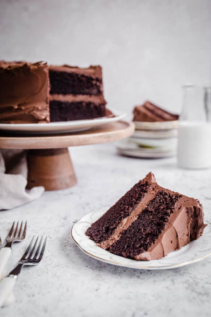 Slice of chocolate cake on a plate in front of whole cake on a stand