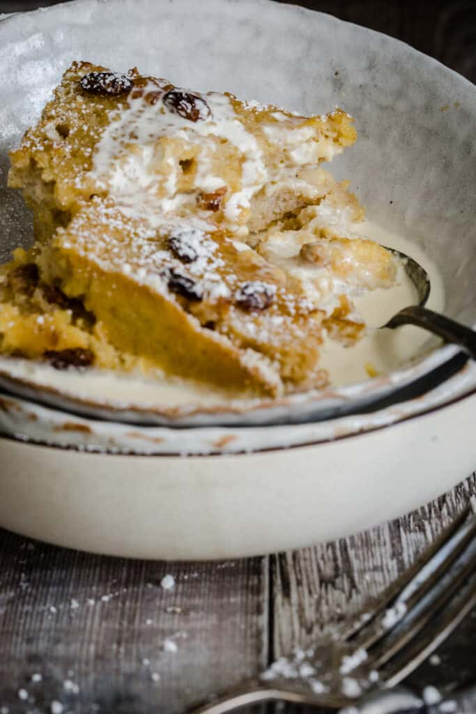 bowl of bread and butter pudding with cream