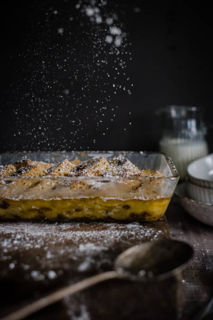 icing sugar being sprinkled on bread and butter pudding
