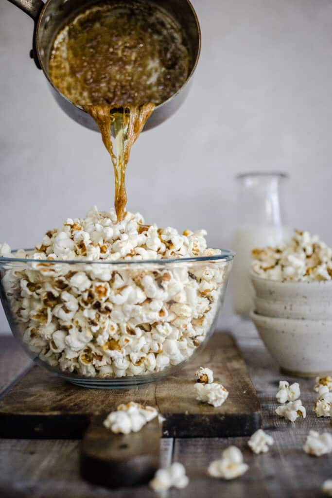 butter being poured over bowl of popcorn
