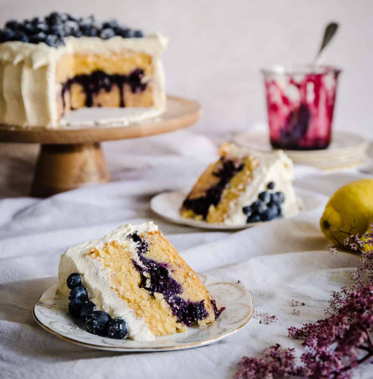 blueberry cake on a wooden stand surrounded by plated up slices of cake
