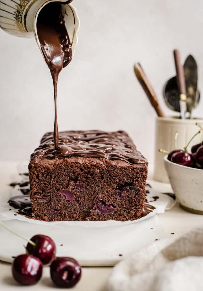 chocolate glaze being poured onto chocolate cherry cake