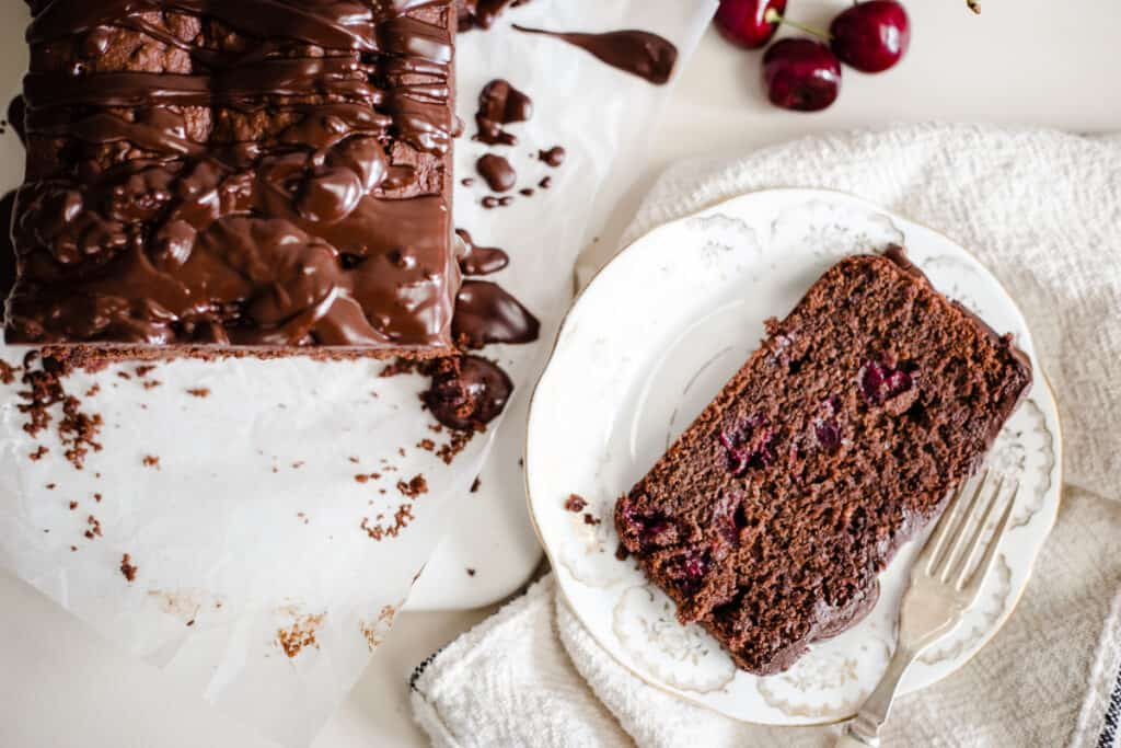 chocolate cherry cake on a plate next to loaf