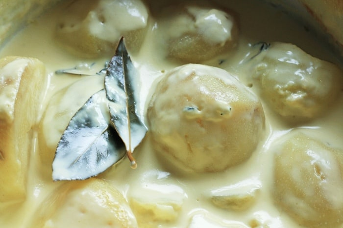 Potatoes poaching in cream with herbs