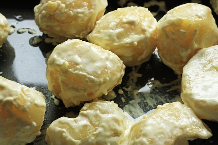 cream baked roast potatoes before roasting on a tray