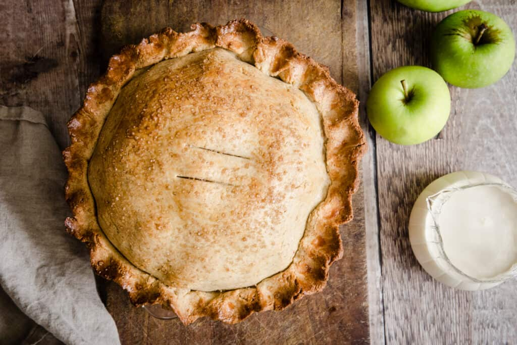 Apple pie on a wooden board next to apples and cream